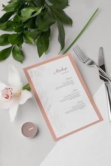 Disposizione piatta del mock-up del menu primaverile con posate e fiori