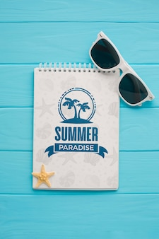 Flat lay summer paradise notepad with sunglasses