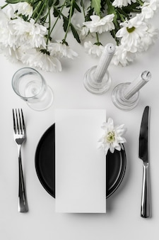 Flat lay of table arrangement with spring menu mock-up on plate and cutlery