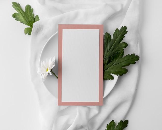 Disposizione piatta della disposizione dei tavoli con mock-up di menu primaverile su piatto e fiore