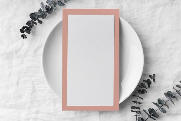 Disposizione piatta della disposizione dei tavoli con mock-up del menu primaverile su piastra e foglie