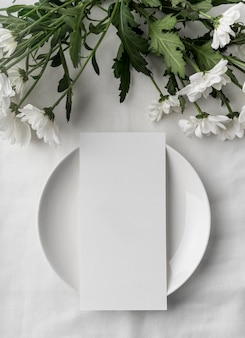 Flat lay of table arrangement with spring menu mock-up on plate and lots of flowers