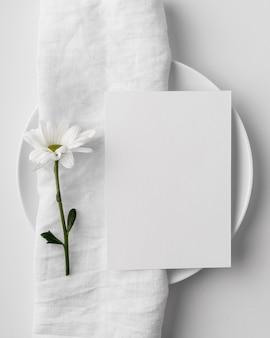 Disposizione dei tavoli piatta con mock-up di menu primaverile su piatto e asciugamano