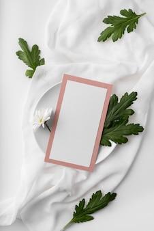 Disposizione piatta della disposizione dei tavoli con mock-up del menu primaverile sul piatto con foglie e fiori