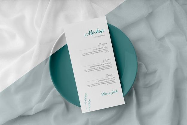 Disposizione piatta della disposizione dei tavoli con mock-up del menu primaverile sul piatto