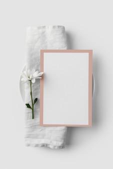Disposizione dei tavoli piatta con mock-up di menu primaverile su asciugamano e fiore