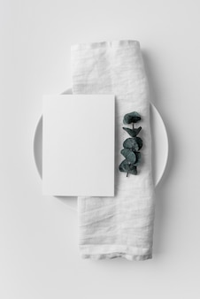 Flat lay of table arrangement with spring menu mock-up and towel on plate