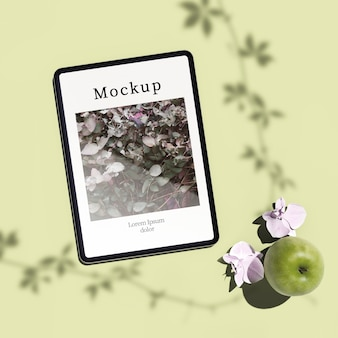 Flat lay of tablet with apple and flowers