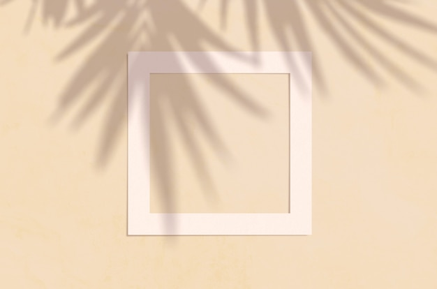 Flat lay top view of creative copyspace with paper white frame and tropical leaves palm shadow on beige color.