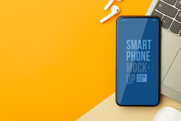 Плоская планировка, вид сверху оранжевый офисный стол с шаблоном макета смартфона и портативный компьютер, беспроводные наушники, мышь. современное рабочее пространство