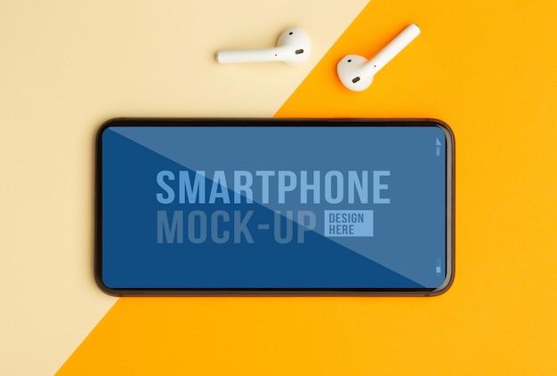 Плоская планировка, вид сверху оранжевого стола в офисе с шаблоном макета смартфона для вашего дизайна и беспроводными наушниками. современное рабочее пространство