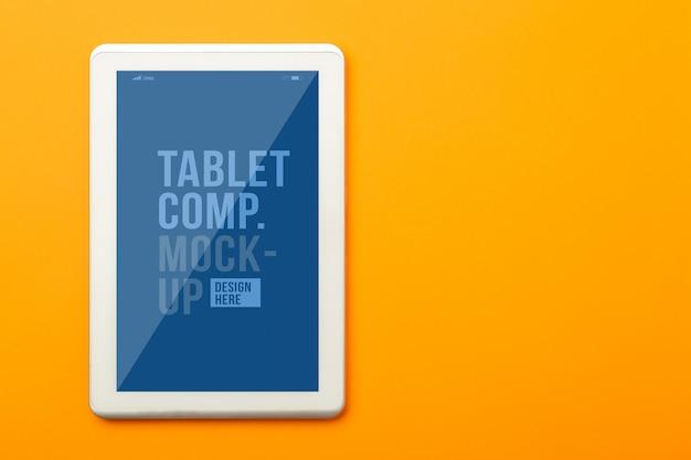 あなたのデザインのタブレットコンピューターのモックアップテンプレートとオレンジのオフィステーブルデスクのフラットレイアウト、トップビュー。モダンな作業スペース