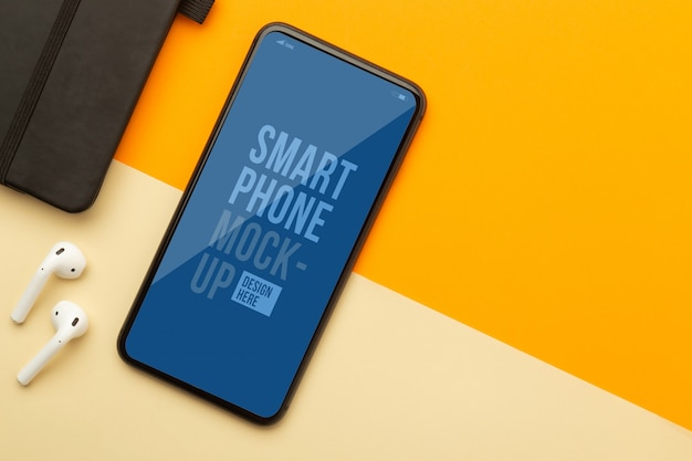 Flat lay, top view of orange office table desk with smartphone mockup template for your design and wireless earphones, notebook.