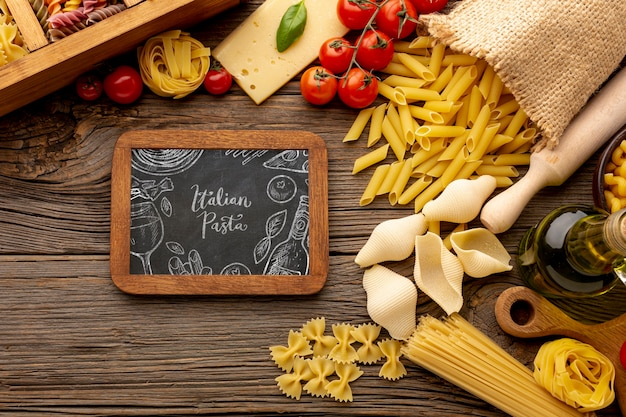 Flat lay uncooked pasta assortment and tomatoes with blackboard mock-up
