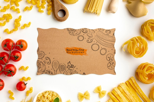 Flat lay uncooked pasta assortment and tomatoes with cardboard mock-up