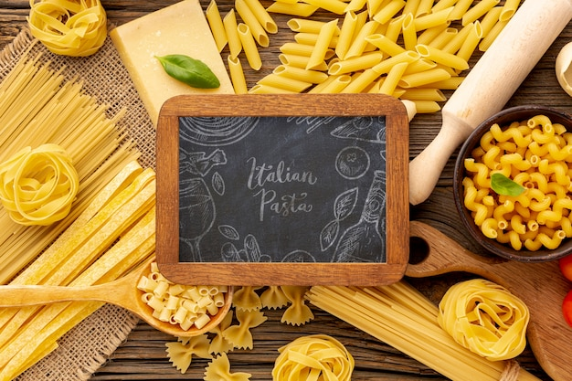 Flat lay uncooked pasta assortment with blackboard mock-up