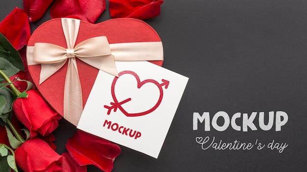 モックアップの手紙とフラットレイバレンタインデーのキャンディーとバラ