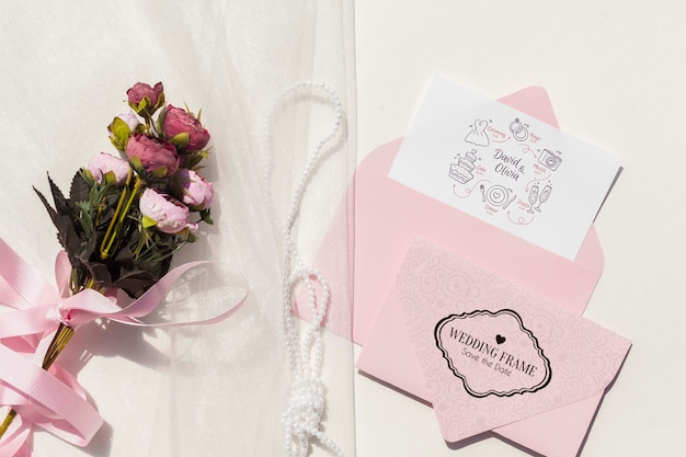 Flat lay wedding ideas with envelope and bouquet of flowers