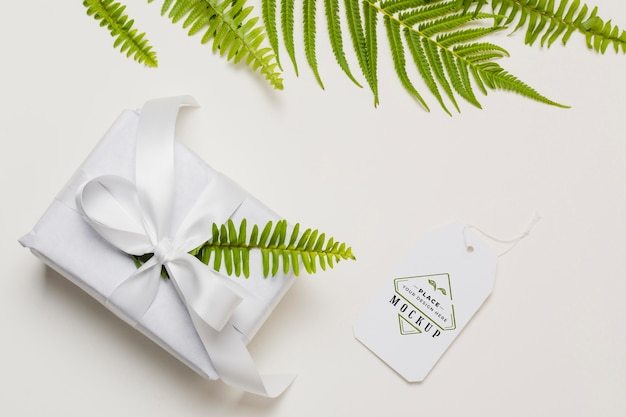 Flat lay white gift with mock-up tag