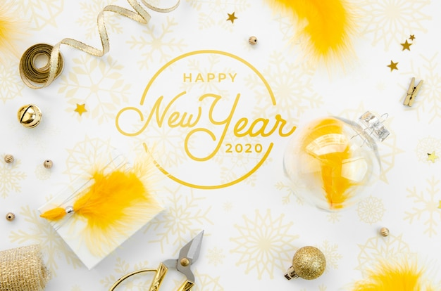 Flat lay yellow new year party accessories and happy new year lettering