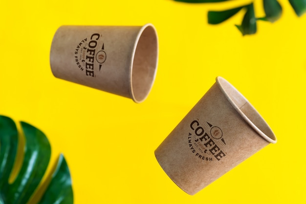 Floating eco friendly paper disposable mockup cups above yellow background with green palm leaves. zero waste