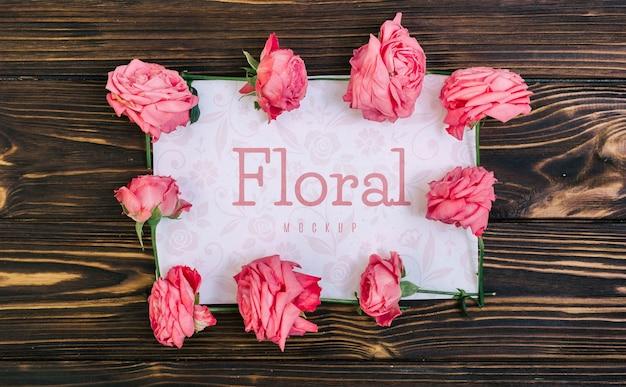 木製のテーブルに花のフレームピンクのバラのモックアップ