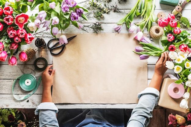 Флорист показывает пустую бумагу для дизайна пространства на деревянном столе
