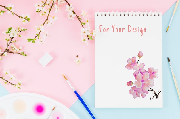Flowers beside notebook with realistic draw