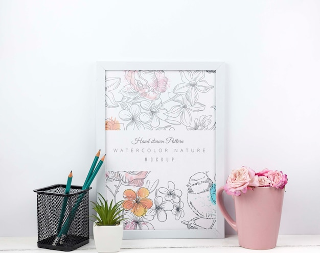Flowers in a cup next to frame mockup