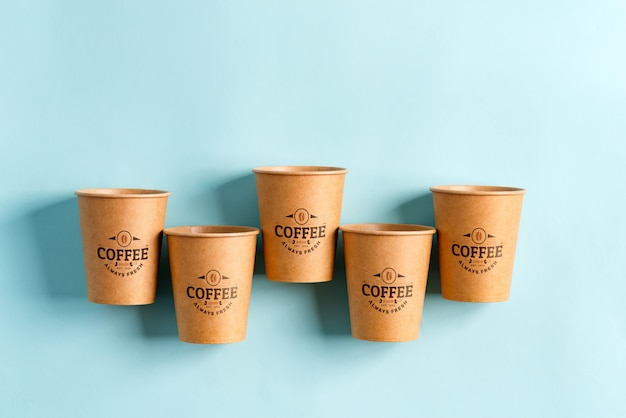Flying eco friendly paper disposable mockup cups above pastel blue background. zero waste