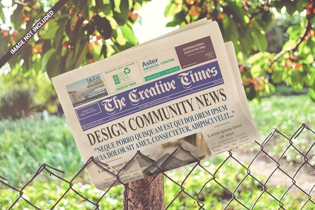 Folded newspaper on the metallic fence mockup