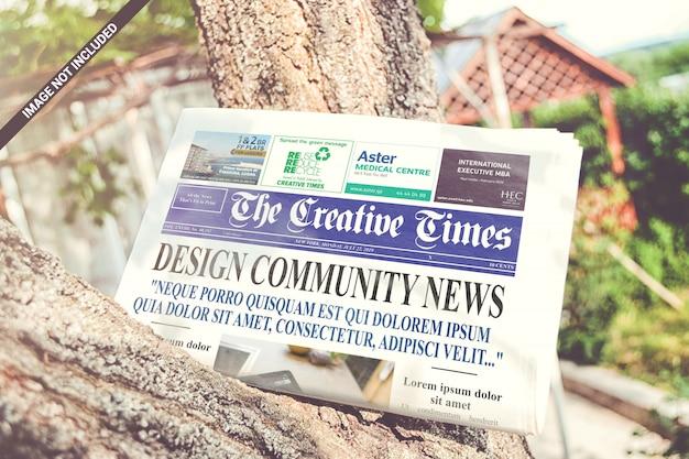 Folded newspaper on the tree mockup