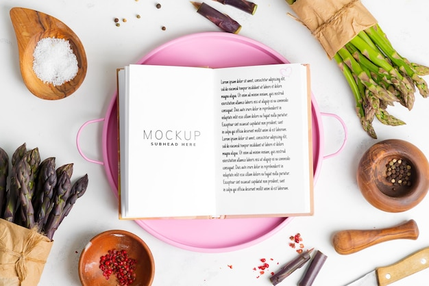 Пищевой фон из бумажной записной книжки для рецепта и свежих домашних натуральных зеленых и фиолетовых овощей спаржи с разными видами на мраморной поверхности.
