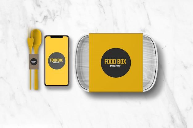 スマートフォンとカトラリーのモックアップを備えたフードテイクアウトボックス