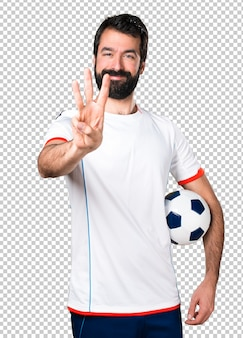 Football player holding a soccer ball counting three