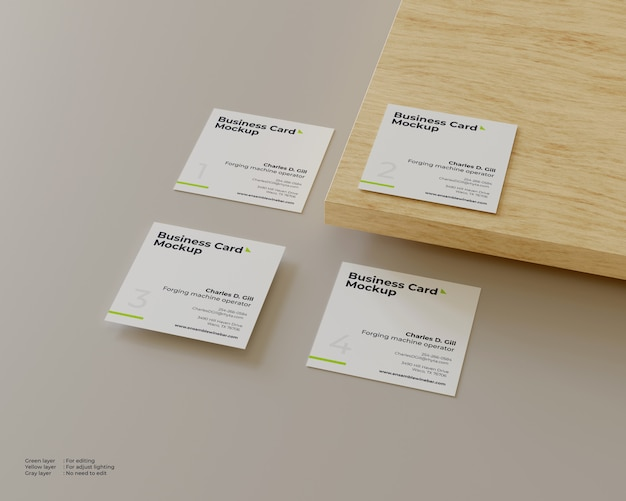 Four business cards mockup one of which is on wood