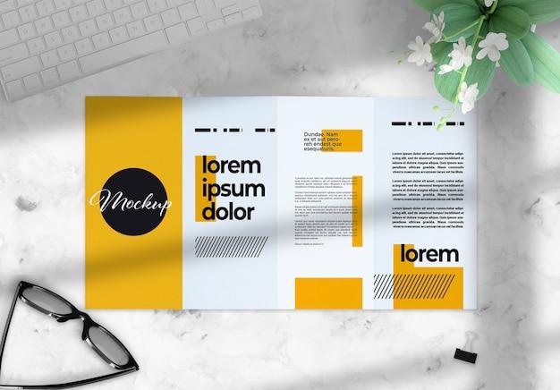 Четырехкратная брошюра на макете рабочего стола с элементами декора