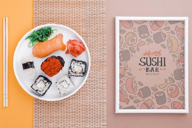 テーブルの上のロール寿司のプレートの横にあるフレーム