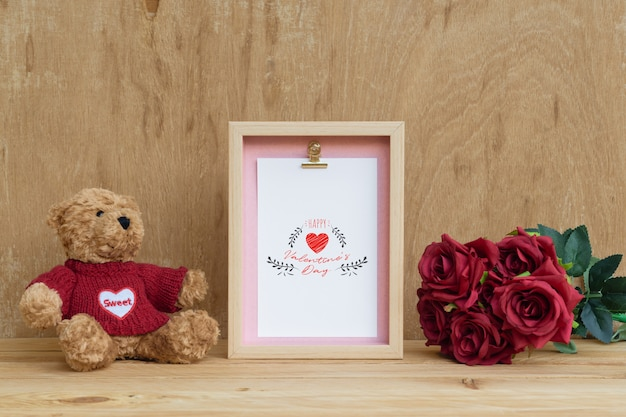 Frame and cute bear with bouquet of red roses mockup