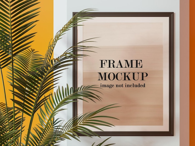 Frame mockup behind palm tree leaves