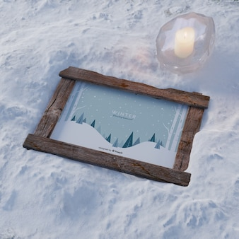 Frame on snow with frozen candle