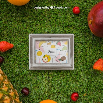 Frame and tropical fruits on grass