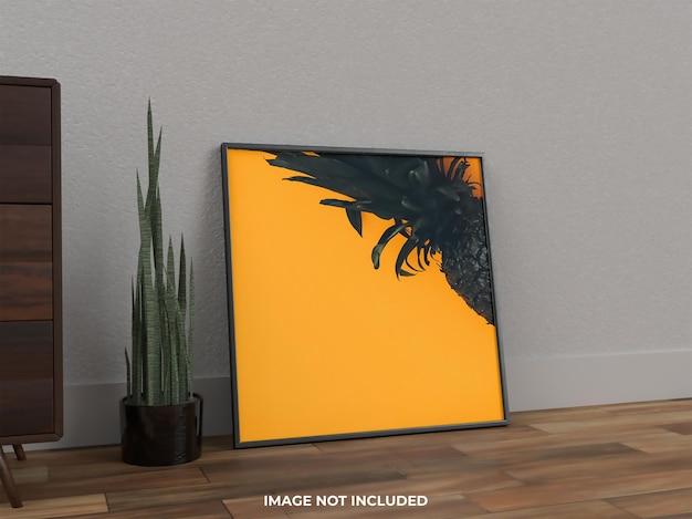 Макет краски в рамке на полу с растением рядом с видом сбоку