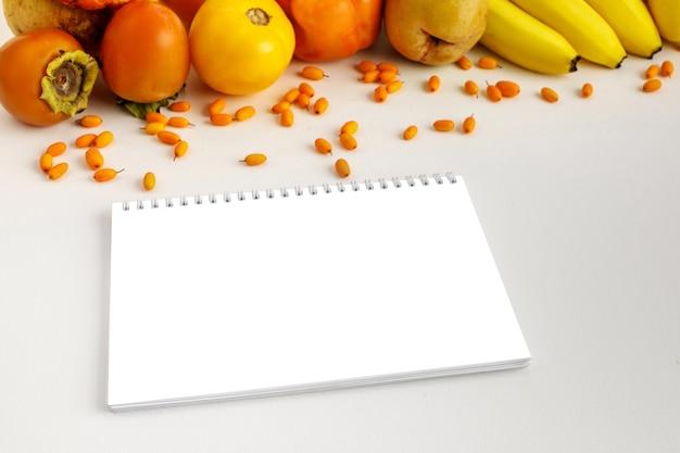 新鮮な秋の黄色とオレンジ色の野菜と果物とノート