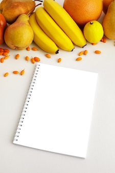 Свежие осенние желтые и оранжевые овощи и фрукты и блокнот