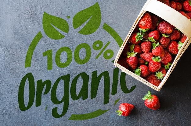 Fresh ripe strawberries in a wooden basket on a dark background. organic juicy berries.