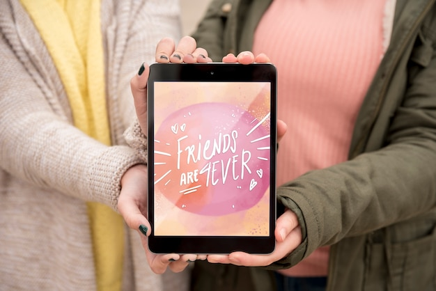 Friend holding happy friendship day tablet
