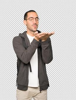 Дружелюбный студент делает жест, отправляя поцелуй рукой