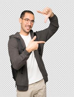 手で写真を撮るジェスチャーをするフレンドリーな学生
