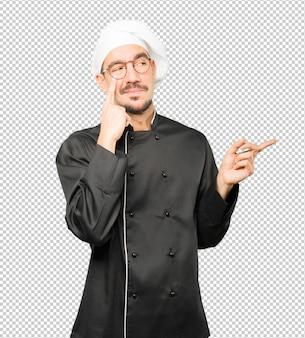 Дружелюбный молодой шеф-повар делает жест осторожности, указывая рукой на глаз